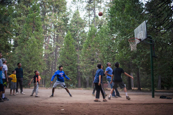 Campers play a pickup game of basketball during downtime before evening prayer.