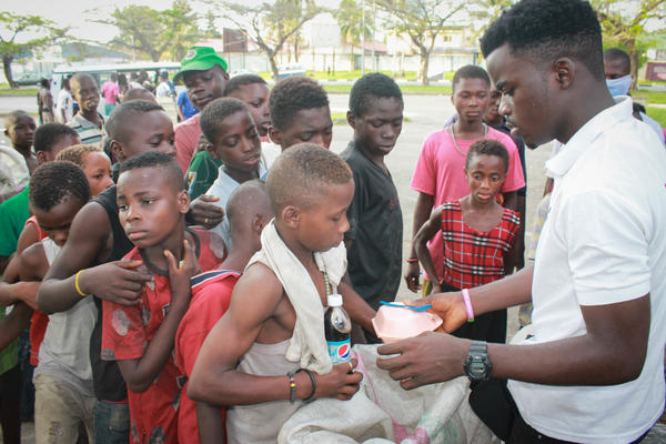 James Okina hands out food to some of Nigeria's street kids.