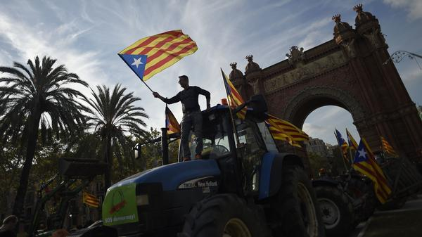Supporters of Catalan independence wave Catalan flags as they drive with tractors through the Arc de Triomf in Barcelona on Tuesday.