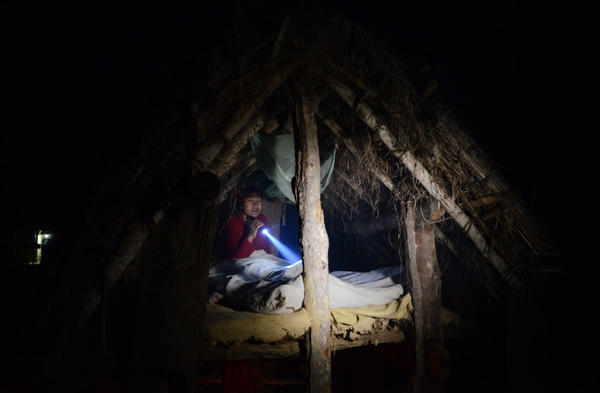 In this photograph taken on February 3, 2017, a Nepalese woman prepares to sleep in a Chhaupadi hut during her menstruation period. The practice of banishing menstruating women from the home — barred from touching food, religious icons, cattle and men — was officially banned a decade ago.