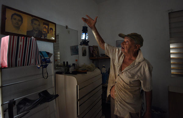 Miguel Quinones, a 93-year-old Korean war veteran, mops up and uses a battery lantern in the darkness of his home due to lack of power.