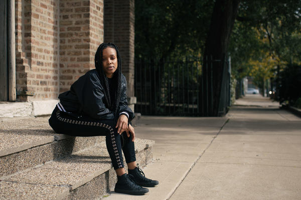 Jamila Woods sits on steps in the Pilsen neighborhood of Chicago, where she lives. Her 2016 solo album <em>Heavn</em> was inspired in part by bell hooks.