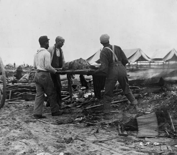 Men carry a body on a stretcher, surrounded by wreckage of the hurricane and flood in Galveston.