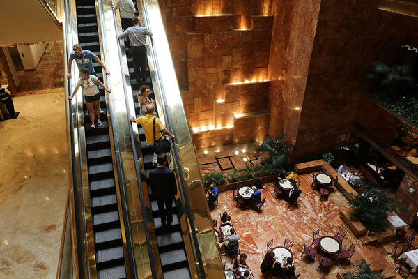 People walk through Trump Tower in New York City in August. Condo prices in the building have fallen, according to journalist and author Tim O'Brien.
