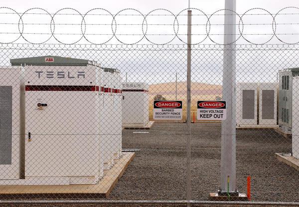 Warning signs adorn the fence surrounding the compound housing the Hornsdale Power Reserve, featuring the world's largest lithium ion battery made by Tesla, during the official launch near Jamestown, Australia, on Friday.