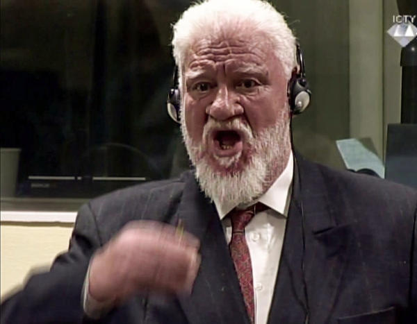 This videograb taken from live footage of the International Criminal Court, shows Croatian former general Slobodan Praljak starting to swallow what is believed to be poison, during his judgement at the UN war crimes court to protest the upholding of a 20-year jail term. Former Bosnian Croat military leader Slobodan Praljak was alive and being treated by medics.