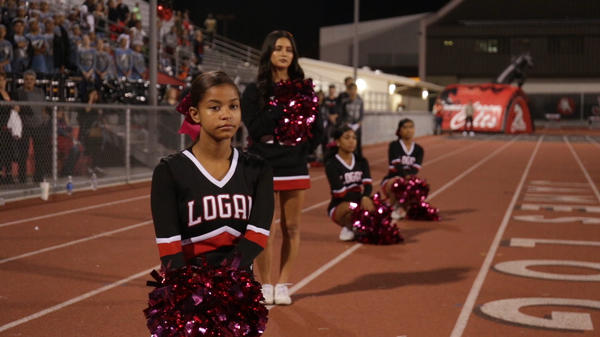 Some teens on the James Logan Colts cheerleading squad take a knee during the national anthem before a football game at James Logan High School in Union City, Calif.
