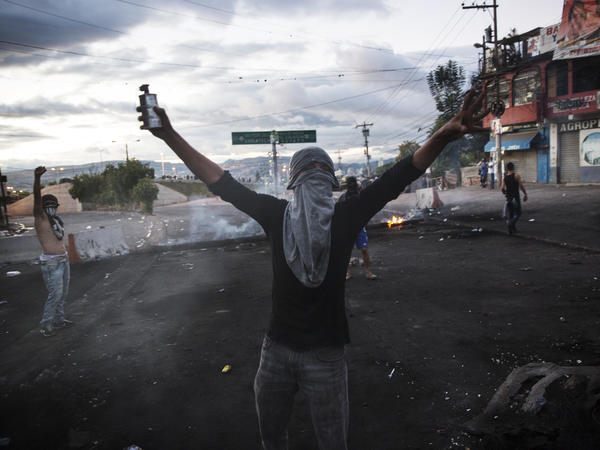 A masked supporter of candidate Salvador Nasralla yells at fellow protesters to fight police at their roadblock to protest what they call electoral fraud in Tegucigalpa, Honduras on Friday.