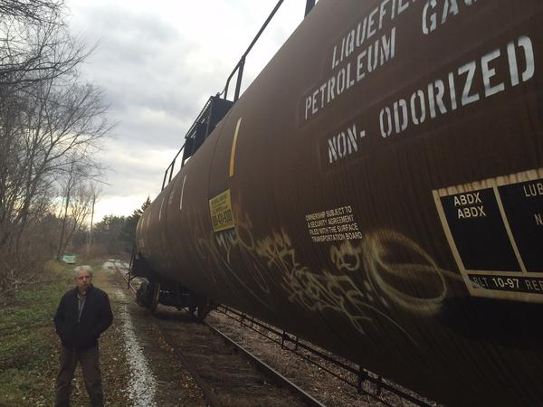 Al Bashevkin walks along the dozens of rail cars filled with liquified propane gas in a neighborhood in Bennington. Under federal rules the trin company is allowed to store the combustible gas near homes.