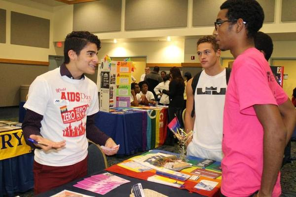 Edwin Serrano, left, a graduate assistant for LGBTQA Initiatives at Florida International University, speaks with sophomores Willy Silva, center, and Joel Batista, at FIU's World AIDS Day 2013 resource fair.