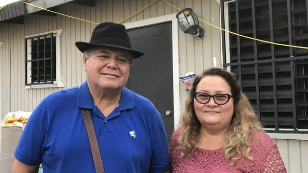 Irma Rivera Aviles and her husband, Ivan Martínez, stand in front of their home last month. Rivera Aviles was ecstatic about the restoration of power to her neighborhood last Friday.