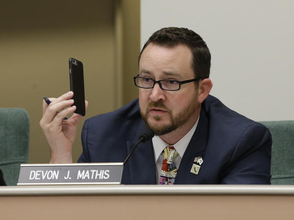 Assemblyman Devon Mathis, R-Visalia, holds up a cell phone as he questions Mark Ghilarducci, director of the California Office of Emergency Services on Monday about communication failures during deadly wildfires in October.