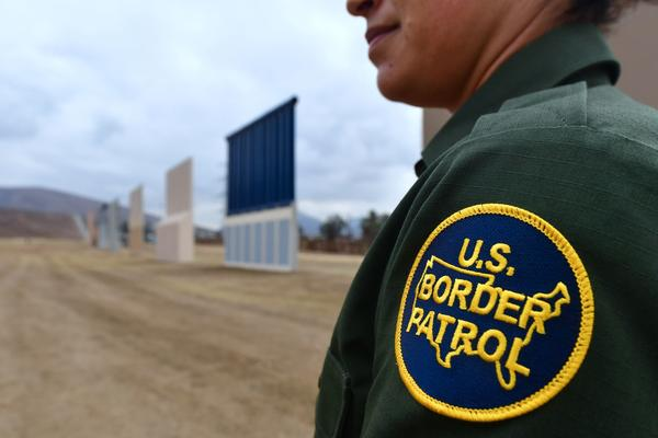 A U.S. Border Patrol officer stands near prototypes of President Trump's proposed border wall in San Diego. Border officers apprehended 310,531 people for being in the country illegally in fiscal 2017, a 25 percent decrease from the year before.