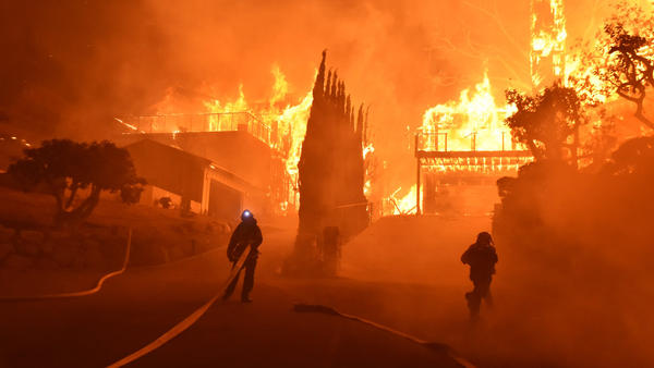 Firefighters work to put out a blaze burning homes early Tuesday in Ventura, Calif.