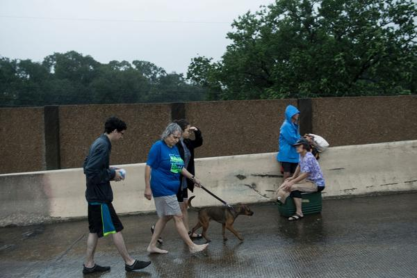 Evacuation residents from the Meyerland area walk onto an I-610 overpass for further help during the aftermath of Hurricane Harvey, Aug. 27, 2017 in Houston, Texas. (Brendan Smialowski/AFP/Getty Images)