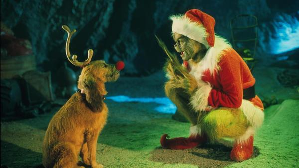 The Grinch, played by Jim Carrey, conspires with his dog Max to deprive the Whos of their favorite holiday in the live-action adaptation <em>Dr. Seuss' How The Grinch Stole Christmas</em>.