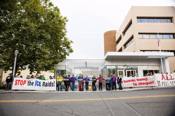 <p>Protesters gather outside the Immigration and Customs Enforcement office in Southwest Portland, Friday, Oct. 11, 2017.</p>