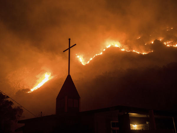 Flames from a wildfire advance down a hillside near the Springs of Life Church in Casitas Springs, Calif.