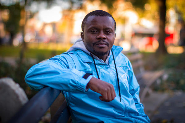 Robert Hakiza, who started a soccer tournament to unite refugees in Africa, sits on a bench in Washington, D.C.