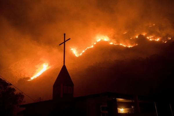 <p>Flames from a wildfire advance down a hillside near the Springs of Life Church in Casitas Springs, California, on Tuesday, Dec. 5, 2017. Wind-driven fires tore through California communities Tuesday for the second time in two months, leaving hundreds of homes feared lost and uprooting tens of thousands of people.</p>