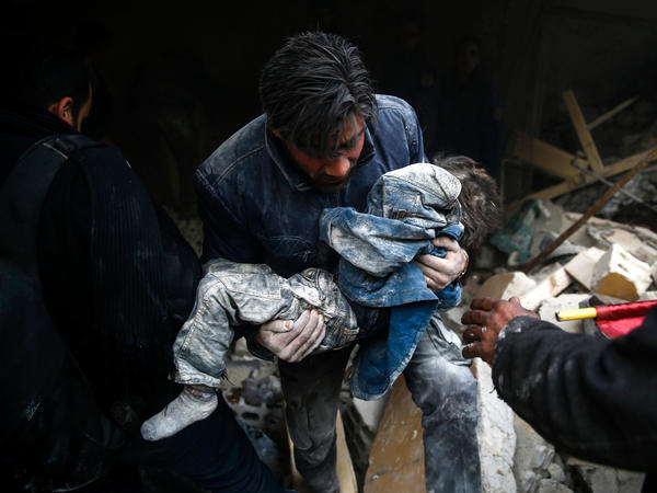 A man evacuates a child from building destroyed by airstrikes in Douma, Syria, in January 2016.