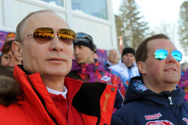 Russian President Vladimir Putin, left, and Premier Dmitry Medvedev watch the men's 4x10 km  cross-country relay at the 2014 Winter Olympics, Sunday, Feb. 16, 2014, in Krasnaya Polyana, Russia. (AP Photo/RIA-Novosti, Mikhail Klimentyev, Presidential Press Service)