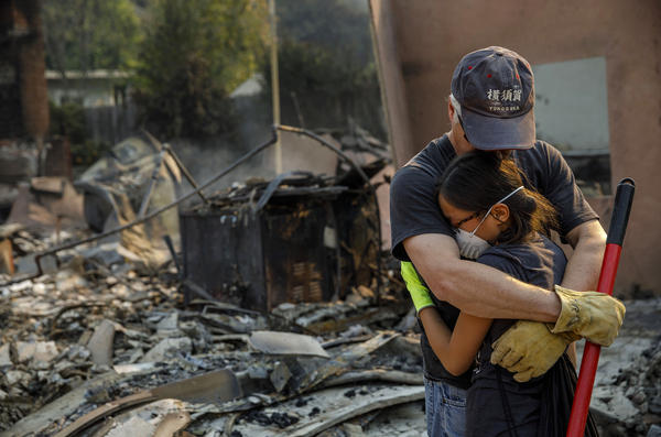 Jeff Lipscomb comforts his daughter Rachel Lipscomb, 11, as they survey their destroyed Ventura home.
