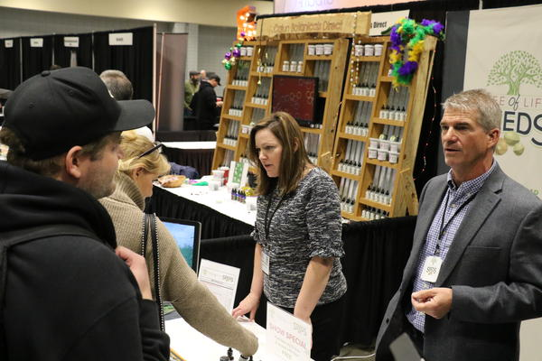 Jeff Morey of Madison, Wisconsin (left) visits with representatives of Tree of Life Seeds, a distributor.