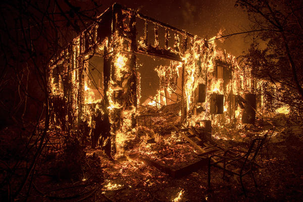 Flames consume a home as a wildfire burns in Ojai, Calif.