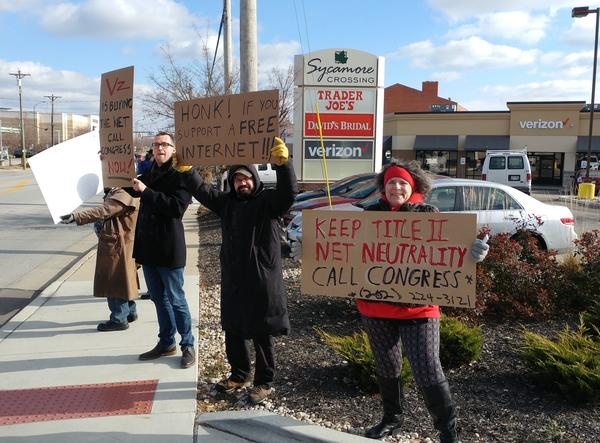 Demonstrators line Montgomery Road protesting the planned repeal of net neutrality.