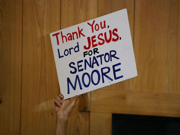 A sign is held up as people attend a campaign rally for Alabama Republican Senate nominee Roy Moore at Fairhope, Ala., earlier this week.