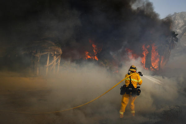 A firefighter battles a wildfire on Thursday at Faria State Beach in Ventura, Calif.