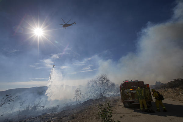 A firefighting helicopter makes a water drop at the Thomas Fire near Fillmore, Calif.