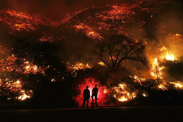 Firefighters monitor a section of the Thomas Fire along the 101 freeway on Thursday north of Ventura, Calif.