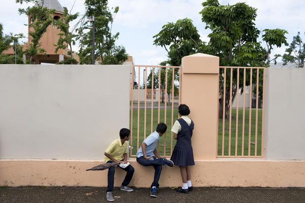 Students peer through a fence at Liberata Iraldo. The school has remained closed for 79 days since Hurricane Maria devastated this Caribbean island, displacing residents.