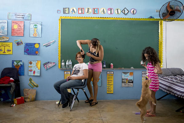 Lilian Garcia braids Melody Vasquez's hair while Garcia's daughter Jaohnliz plays with her dog, Fanny, inside Liberata Iraldo, a middle school in Rio Grande, where they sought shelter after Hurricane Maria.