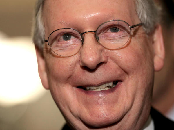 Senate Majority Leader Mitch McConnell smiles while talking to reporters. The GOP tax bill he's shepherding passed the Senate and is now being reconciled with the House.