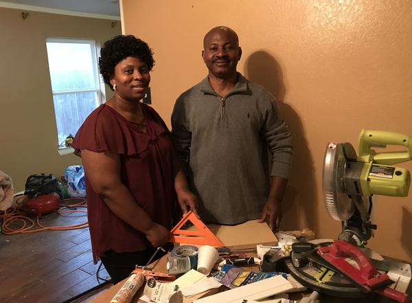 Tosha Atibu and her husband Atibu Ty Ty stand in their Houston home, which was flooded during Hurricane Harvey. They are racing to get it shape in time for the family to move back in for Christmas.