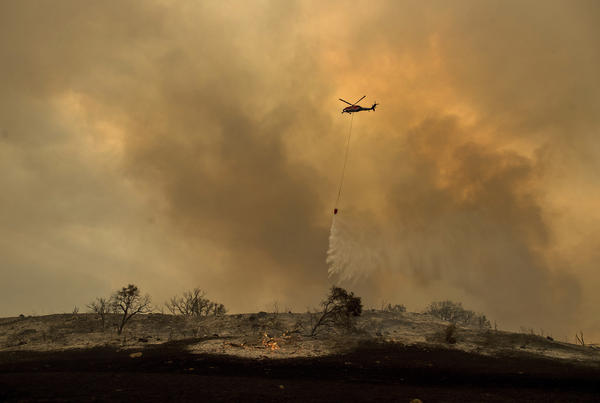A helicopter drops water on the Thomas Fire near Ventura, Calif., on Saturday.