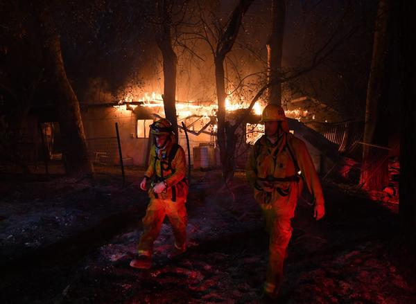 Firefighters move away from a burning house after discovering downed live power lines, as the Thomas wildfire continues to burn in Carpinteria, Calif., on Dec. 10, 2017. (Mark Ralston/AFP/Getty Images)