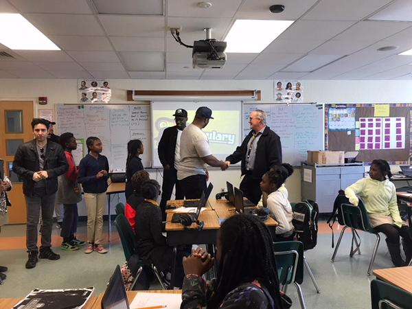 Kev Marcus shakes Mr. O'Brien's hand as he and Black Violin partner, Wil B, greet his fourth grade class.