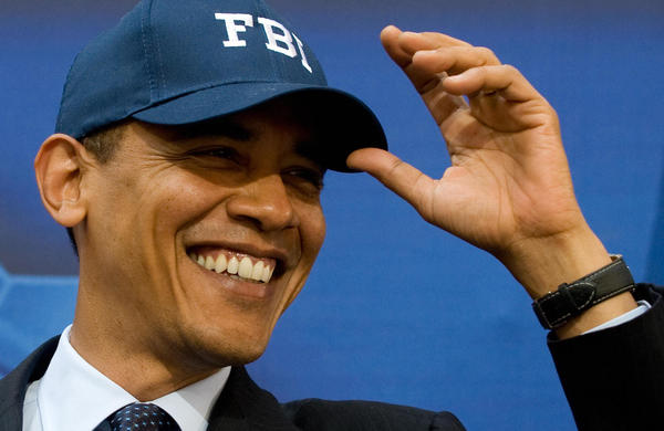 Then-President Barack Obama wears an FBI hat given to him by then-FBI Director Robert Mueller before speaking to employees at FBI Headquarters in Washington, D.C., in April 2009.