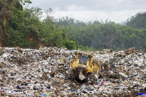 The active part of the landfill in Toa Baja is currently a hot, rancid, open dump. Federal regulations require trash piles to be covered daily with earth. But the site's supervisor says that's currently impossible.
