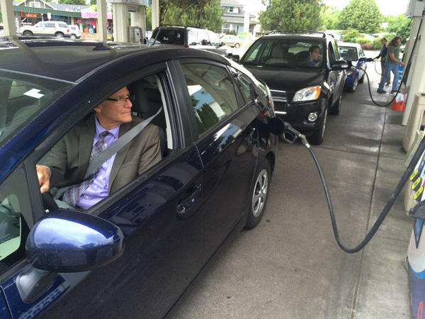 Oregon Department of Transportation Spokesperson Tom Fuller fills his tank at a gas station in Salem, Oregon.
