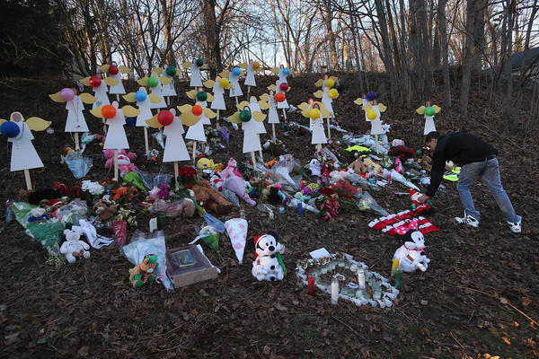A man places a plush Santa at a makeshift memorial for Sandy Hook shooting victims in 2012 in Newtown, Connecticut.