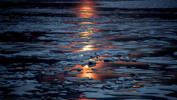 The midnight sun shines across sea ice along the Northwest Passage in the Canadian Arctic Archipelago, July 23, 2017.