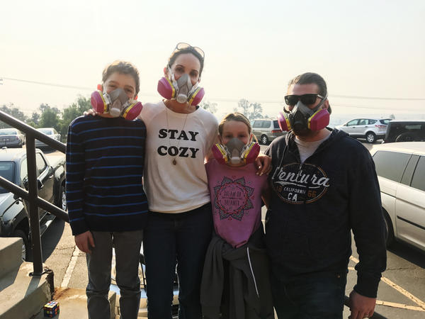Nancy and Jay Blomquist stand outside the Local Assistance Center in Ventura, Calif., with their twins, Alexander and Olivia. The family wears masks to protect themselves from the ash and smoke in the air from the Thomas Fire.