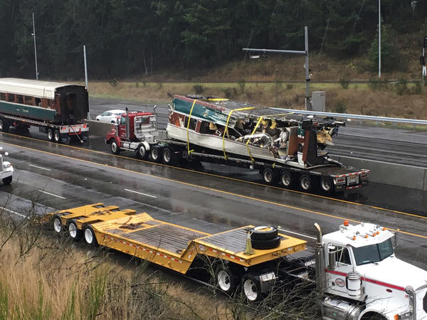 Derailed Amtrak train cars that were previously dangling over I-5 have now been loaded onto flatbed trucks.