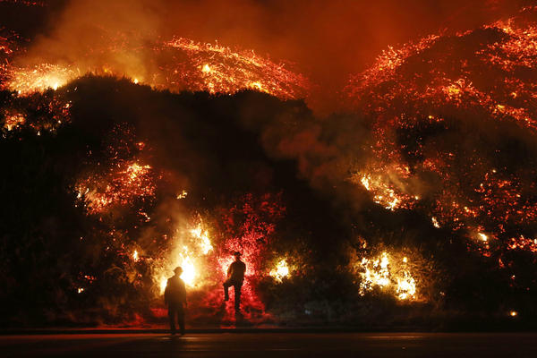 Firefighters monitor a section of the Thomas Fire along the 101 freeway, north of Ventura, Calif., on Dec. 7.