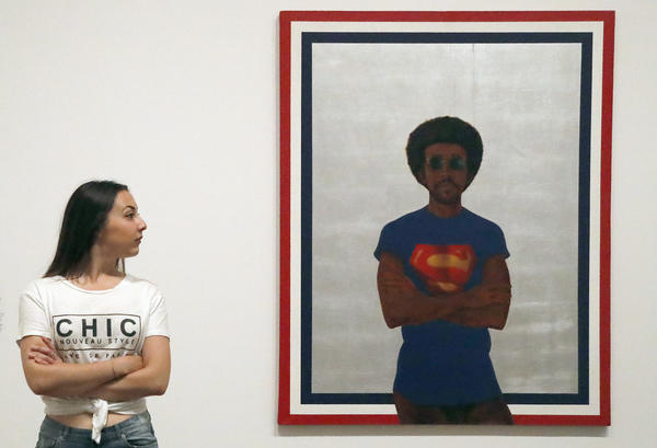A woman poses beside Barkley Hendricks painting, 'My Man Superman (Superman never saved any Black people)' at the exhibition Soul of a Nation, exploring the art made by African American artists between 1963 and 1983, in London.